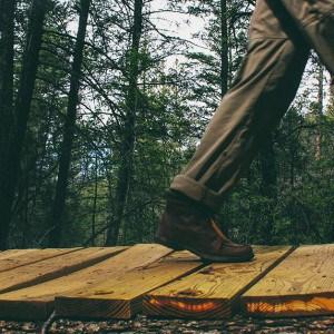 hiker walks across a wood board walk in the forest