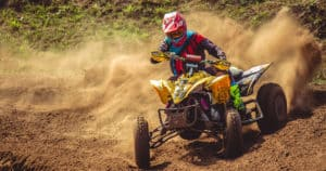 ATV kicks up dirt around a turn