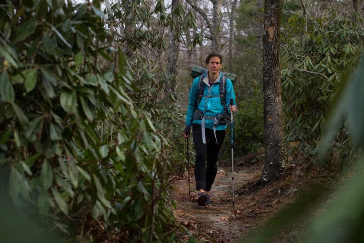 Jennifer Pharr Davis hikes single track through wooded area.