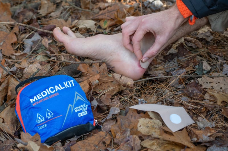 Hiker treats a blister on a fall hike.