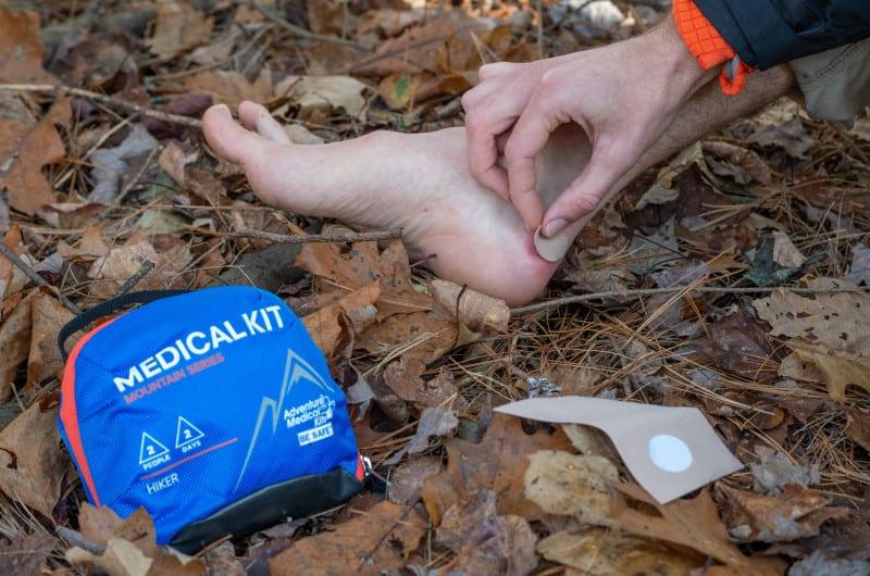 Hiker treats a blister on a fall hike.