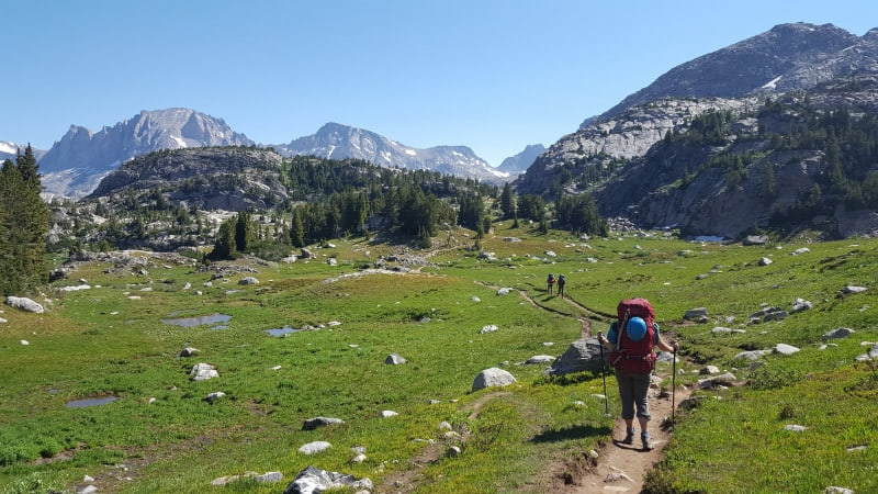 three backpackers cross a high mountain meadow on a hiking adventure.