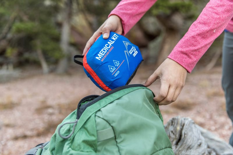 A hiker prepares for a hiking adventure by packing a Hiker Adventure Medical Kit.