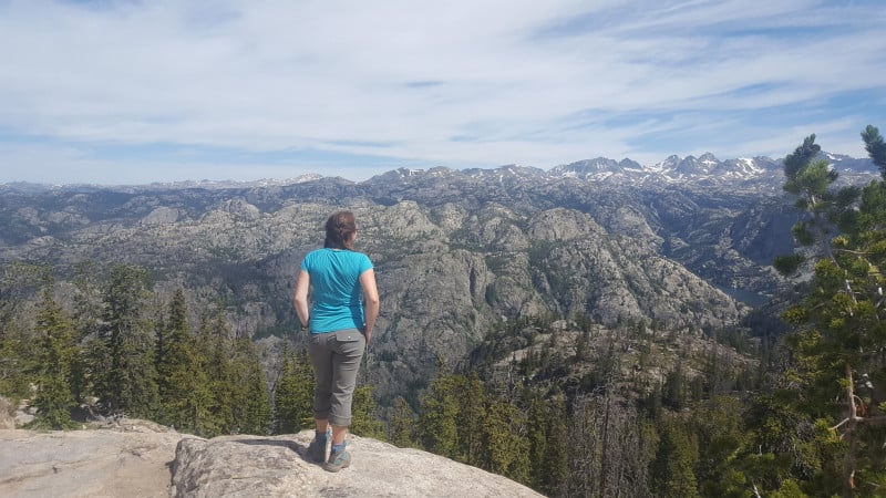 A hiker is rewarded with a wide open view of snow-capped mountains and craggy hills.