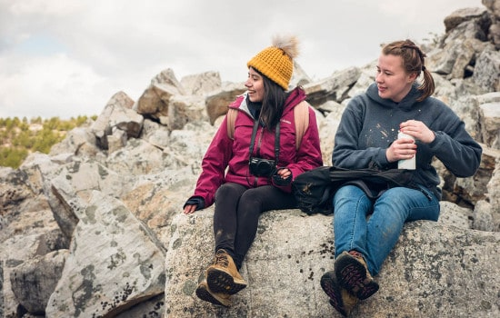 Two hikers take a break on top of a boulder field.