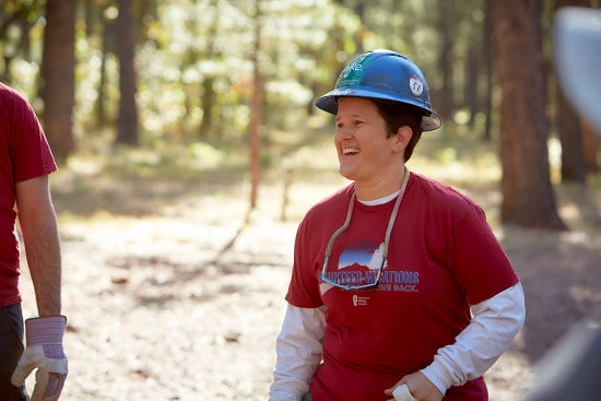 American Hiking Society volunteer with hard hat and gloves laughs.