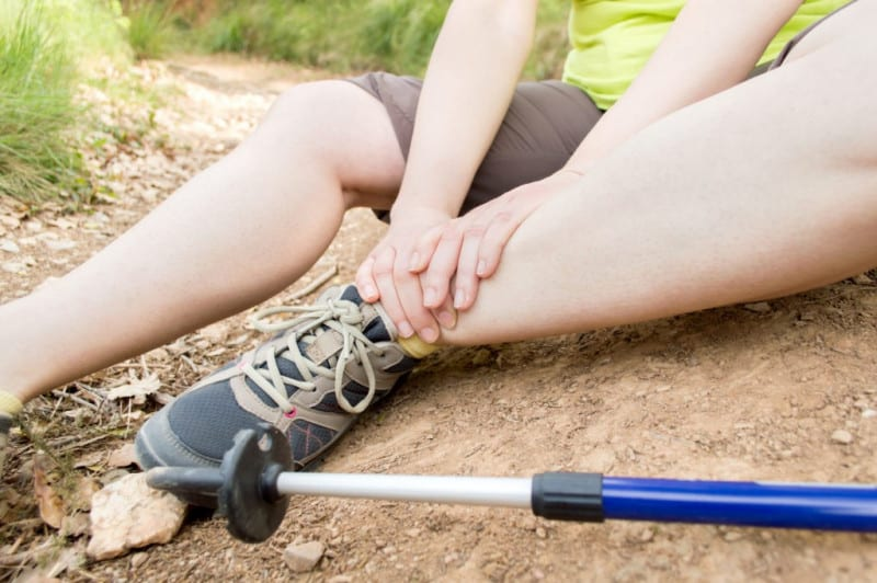 Hiker with a sprained ankle sits along a trail.