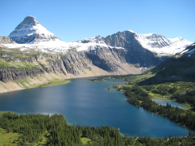Snow capped alpine peak sits at the edge of a deep blue sub-alpine lake in Glacier National Park.