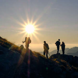 group of hikers stand on an alpine ridge under a sunburst