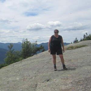 Sarah Baker Morgan standing on large rock slab overlook