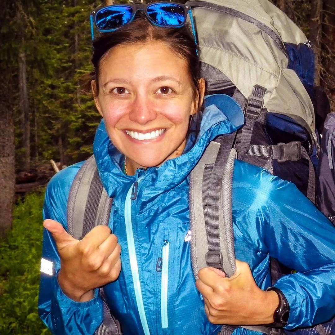 Heather Distad gives a thumbs up while backpacking