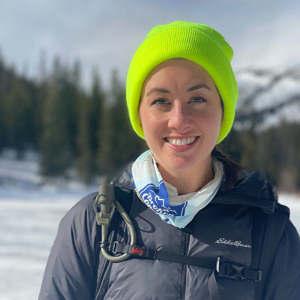 Kelsey Olsen wears a lime green hat in a winter portrait