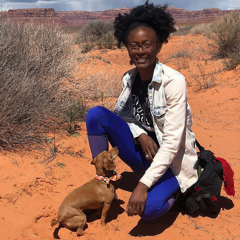 Latasha Dunston outdoor portrait kneeling in a sandy desert valley.