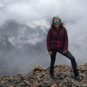 Maria Betancourt stands on the summit of Redcloud Peak