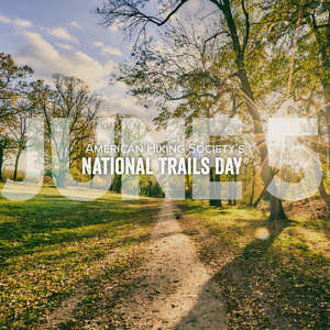 American Hiking Society's National Trails Day: June 5 text overlay on golden light illuminates a straight gravel trail that runs through a city park