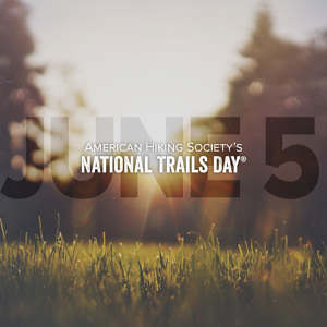American Hiking Society's National Trails Day: June 5 text overlay on green grass backlight in a park