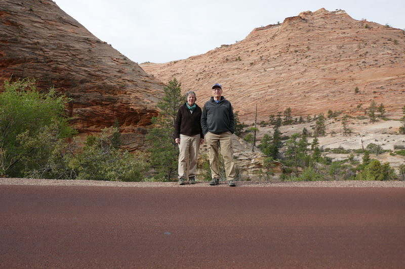 Two people stand on the side of a trail in front of desert hills in the Grand Canyon.