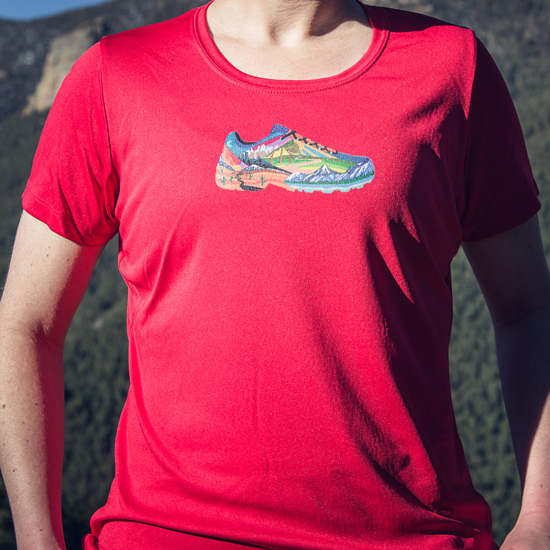 red t-shirt with an illustration of multiple hiking scenes within a trail shoe