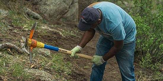 Get invloved - Man swings pick mattock while maintaing a trail